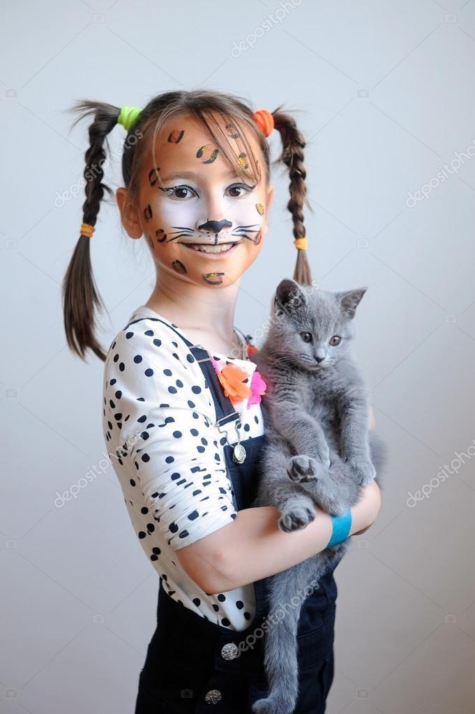 Ritratto dolce di una bambina sveglia con la faccia dipinta come un leopardo che tiene un gattino grigio