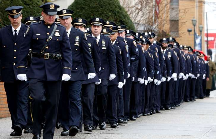 New York City police officers march before funeral services for police officer Wenjian Liu at Aievoli Funeral Home, Sunday, Jan. 4, 2015, in the Brooklyn borough of New York. Liu and his partner, officer Rafael Ramos, were killed Dec. 20 as they sat in their patrol car on a Brooklyn street. The shooter, Ismaaiyl Brinsley, later killed himself.