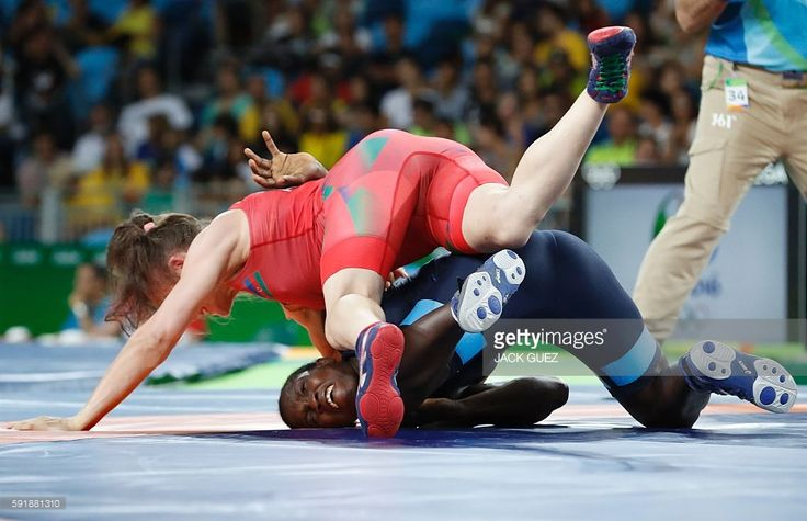 Azerbaijan's Natalya Sinishin (red) wrestles with Senegal's Isabelle Sambou in their women's 53kg freestyle repechage round 2 match on August 18, 2016, during the wrestling event of the Rio 2016 Olympic Games at the Carioca Arena 2 in Rio de Janeiro. / AFP / Jack GUEZ
