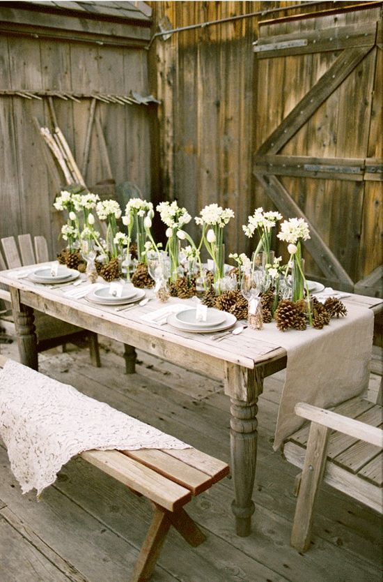 Skip the pine cones, but do lines of flowers along long tables, so easy and so impressive.  Could be any flowers!