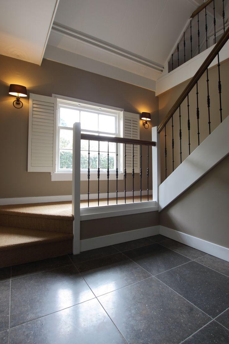 Houten trap met bordes met sissal bekleed, zwarte spijltjes en houten leuning.