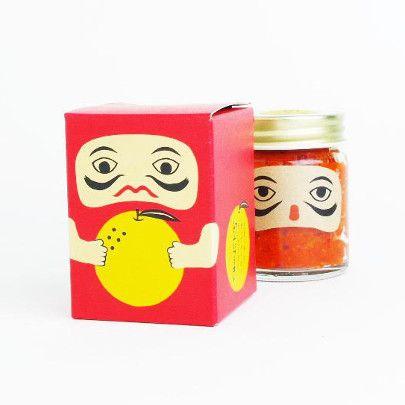 岡山県高梁市で生産された唐辛子と柚子を使用した、無添加の柚子胡椒。この「紅だるま」は、紅の染料である「ベンガラ」の生産で有名な岡山県高梁市の吹屋地区で作られています。吹屋地区はベンガラの色である赤色を多く使った製品がたくさんあり、この紅だるまもベンガラの赤にちなんで赤唐辛子を使っているのが特徴の一つ。 柚子も白い部分が入ってしまうと苦くなるので、表面の皮のみしか使わないというこだわりの逸品です。そのため、蓋を開けたときに広がる柚子の香りは、ほかの柚子胡椒では味わえないフレッシュな柚子の香りと風味があります。質感もほかの柚子胡椒と比べてソフトで柔らかいため、汁物にもよく溶けて、料理にも使いやすくなっています。一般的な柚子胡椒に比べて辛みは強いですが塩分が少ない為、普段、柚子胡椒が苦手な方でもお召し上がりいただけます。上品な辛みと爽やかな柚子の香りを、どうぞお楽しみください。