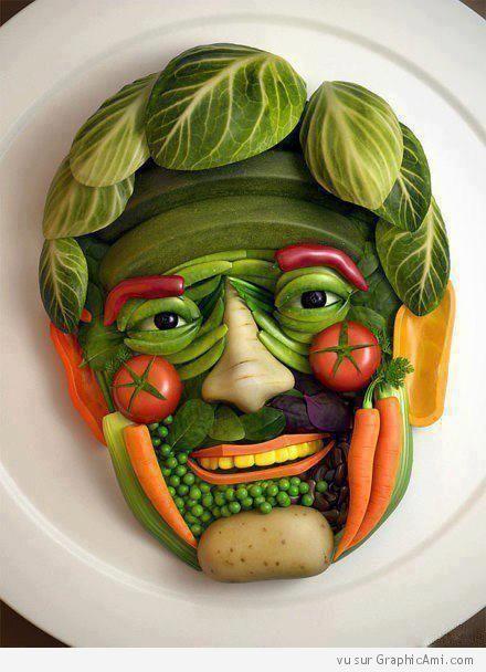 Visage souriant constitué de légumes divers : carottes, petits pois, tomates, pommes de terre, maïs, haricots et courgettes.