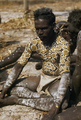 Australia | An Aboriginal dancer sits patiently while others paint his back. Arnhem Land, Northern Territory | ©Howell Walker