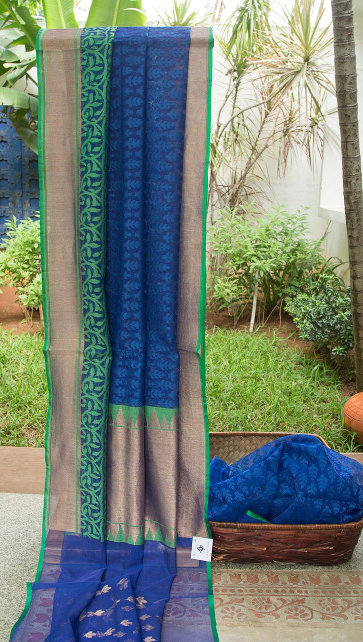 This Benares net sari is in navy blue with small bhuttas all over in royal blue thread work. The border is in navy blue with floral pattern and temple borders woven in emerald green and gold zari. …