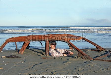 Man sits in rusted car wreck buried in sand on Waitarere Beach in New Zealand