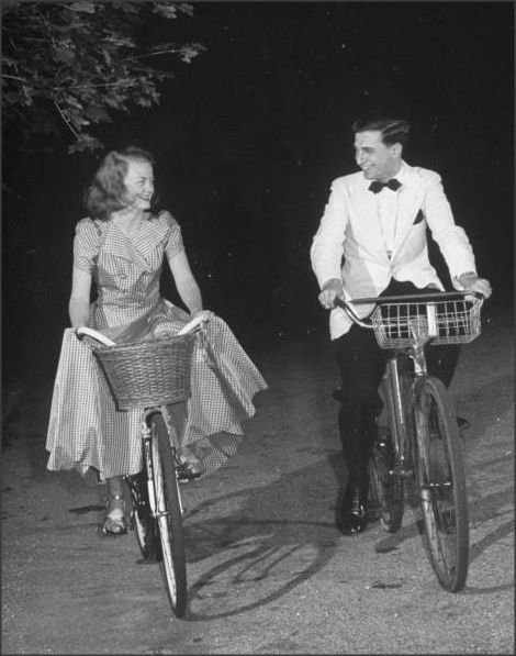 Young suburban couple riding bicycles to formal dance, 1942
