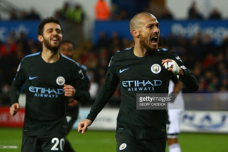 Manchester City's Spanish midfielder David Silva (R) celebrates after scoring their third goal during the English Premier League football match between Swansea City and Manchester City at The Liberty Stadium in Swansea, south Wales on December 13, 2017. / AFP PHOTO / Geoff CADDICK / RESTRICTED TO EDITORIAL USE. No use with unauthorized audio, video, data, fixture lists, club/league logos or 'live' services. Online in-match use limited to 75 images, no video emulation. No use in betting…