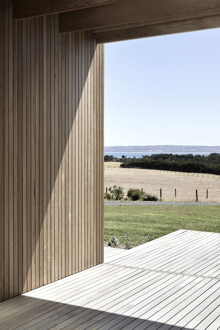 On a gentle rise looking toward the distant Victorian coastline sits a timber-clad building, clearly contemporary yet so thoughtfully designed that it resonates in tune with its natural setting. While the elevations are consistent, calling to mind the unmistakable silhouette of a rural barn, the project by Tom Robertson Architects actually consists of two pavilions that mirror each other, joined by a central breezeway.