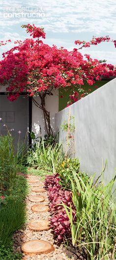 Feito pelo casal, o paisagismo do corredor lateral do sobrado preseva o clima de interior, reforçado pelo portão baixinho, autêntico.
