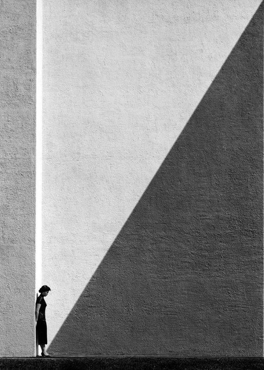The composition of this image is very good as the individual has been placed on the left hand side to differentiate away from the abstract lighting, altogether making the image visually more striking. The use of monochrome really adds to the dramatic feel of the image as it looks like the individual is torn between both good and bad sides. The fact the individual is also smaller than the rest of the image makes the photograph more central around her.