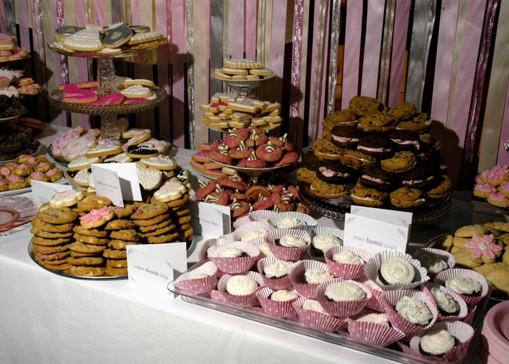 a cookie table with a pink silver ribbon wall