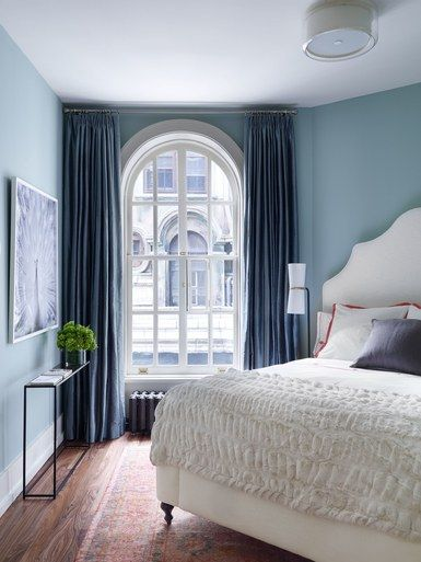 Also overlooking Broadway, a guest bedroom is home base for the clients' daughters when they come to visit. The antique carpet is a Turkish Oushak circa 1880, while the custom curtains are made from a Thai silk by Holland & Sherry | archdigest.com