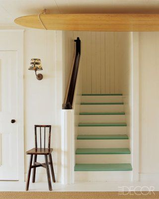 Designer Kerry Joyce painted the steps of a staircase in playful ocean-green Bezique by Pratt Lambert Paints for an actress's family home in Malibu, California. The sconce and surfboard tied to the ceiling reiterate the home's lighthearted, seaside vibe.