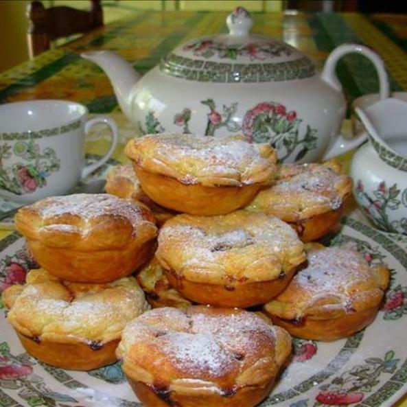 Cheesecakes Assados:  230 g. de massa folhada (pode ser pronta), -110 g. de queijo curado, ou 110 g. de queijo cottage peneirado, -50 g. de açúcar mascavo, -2 ovos grandes, batidos, -2 colheres de sopa de creme de leite, -1 colher de sopa de água de flor de laranjeira ou 1 colher de sopa de água de rosas, -75 g. de amêndoas moídas, -50 g. de frutas secas mistas (como por exemplo uva passas, tâmaras e damascos), picadas, cristalizadas e sem sementes, – açúcar de confeiteiro, peneirado para…