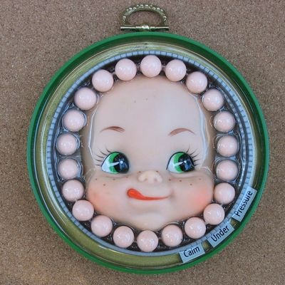 Calm under pressure:Upcycled Doll Art by gjarvisjewelryetc.A little wall hanging to watch over you during those stressful days, this charmer is made from a couple of large plastic jar caps, a vintage doll, and other found objects cast in resin.