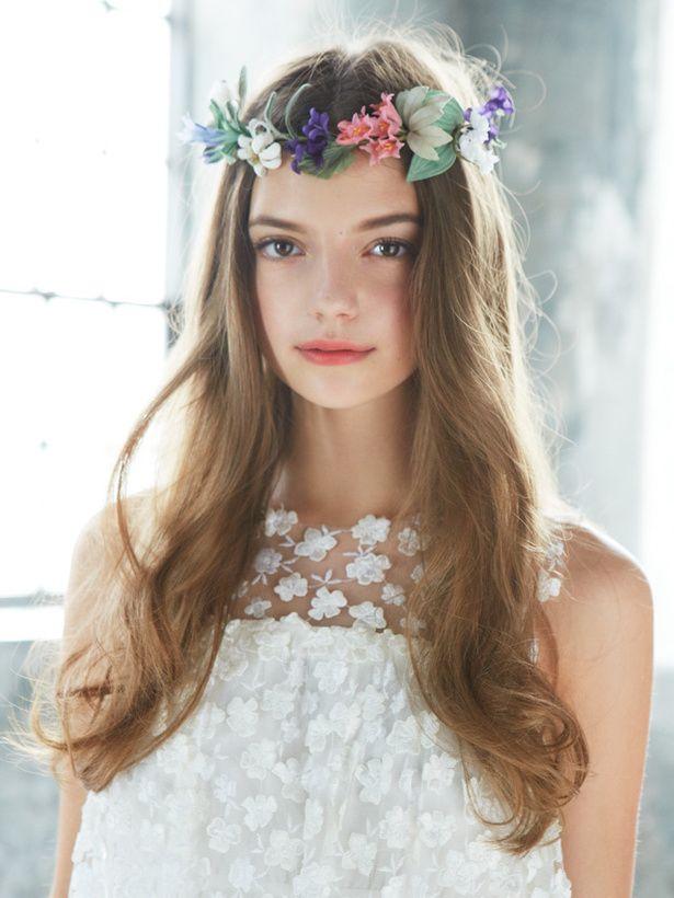 野原に咲く花を象った花冠をのせた、ナチュラルなダウンスタイル。毛先にゆるめのウェーブをかけ、甘くなりすぎないようにするのがポイント。花のレー...