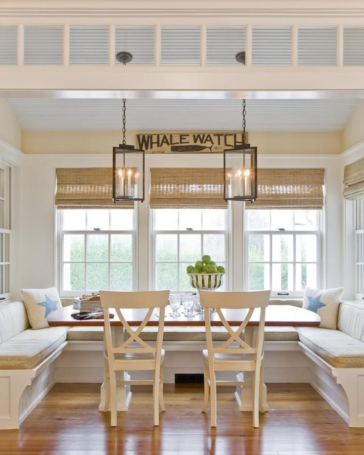 The beadboard ceiling and window bay in the kitchen's dining nook are reminiscent of an old-fashioned porch. A banquette provides seating at the custom trestle table. The sizable lanterns were crafted by Authentic Designs of West Rupert, Vermont.