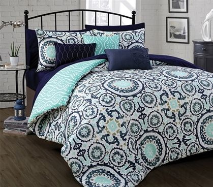 Shop at DormCo for our Leona Twin XL Comforter. This dorm necessities item has a gorgeous, intricate pattern with navy, white, and mint colors in the theme for a Twin XL Comforter that is eye catching  and creates a beautiful dorm room decor style.