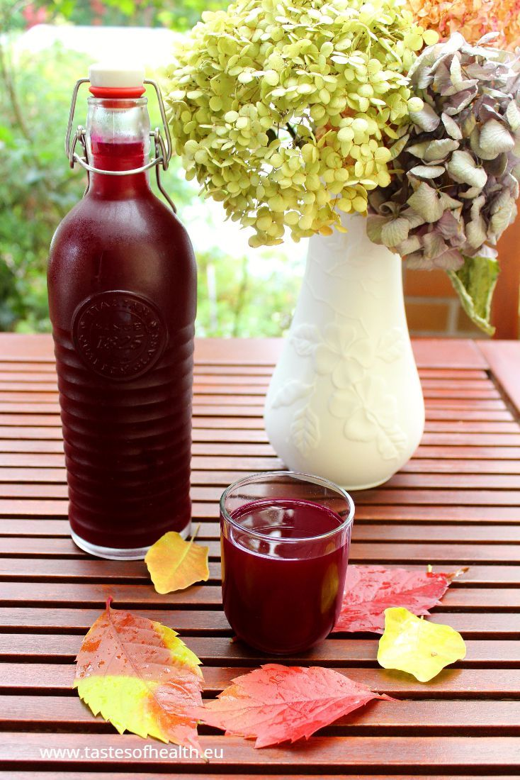 An image of Fermented Beet Kvass in a bottle and in a glass. There are blooms in the white vase in the background.