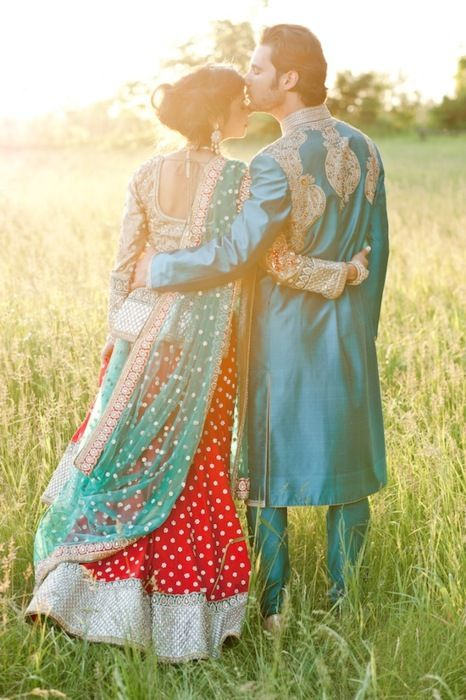 Cute Indian groom, kissing his bride on the forehead.