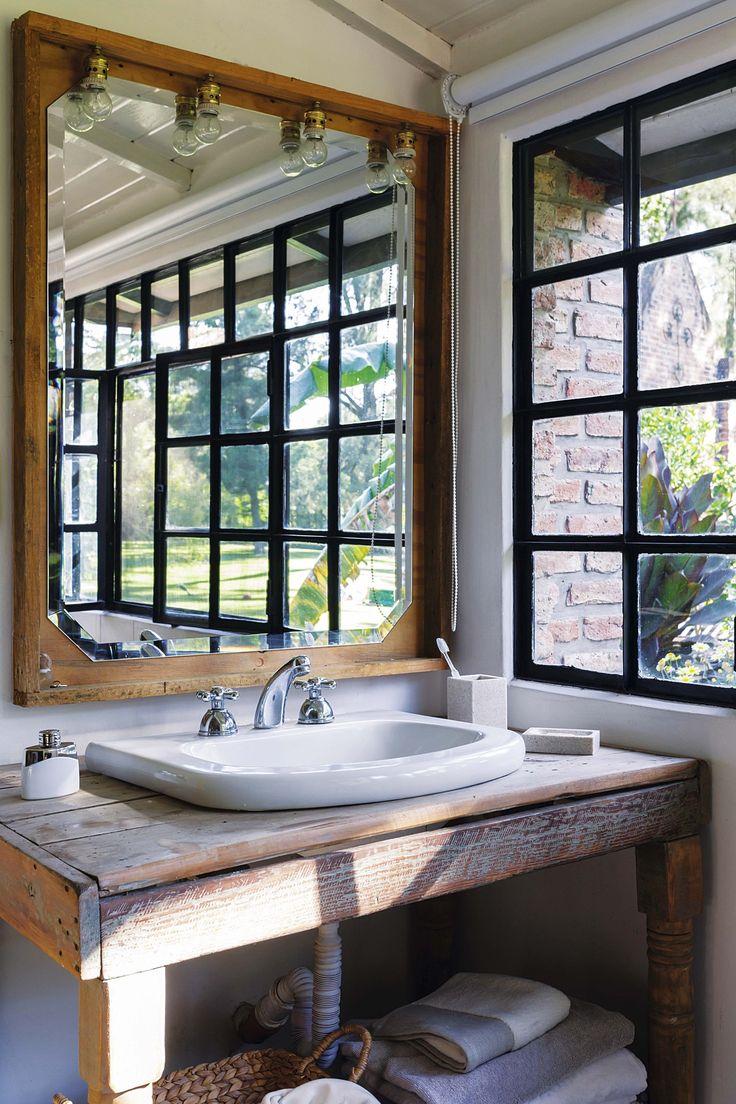 Baño rústico y simple, con luz natural y ventana al jardín en una casa moderna en un country.