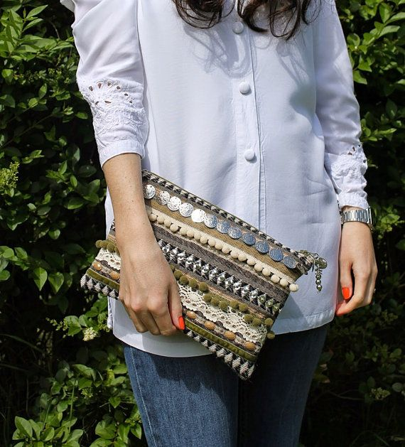 This zip clutch has been hand made using reclaimed textiles. The exterior is a woven wool fabric with an ethnic geometric design.    The front of the bag
