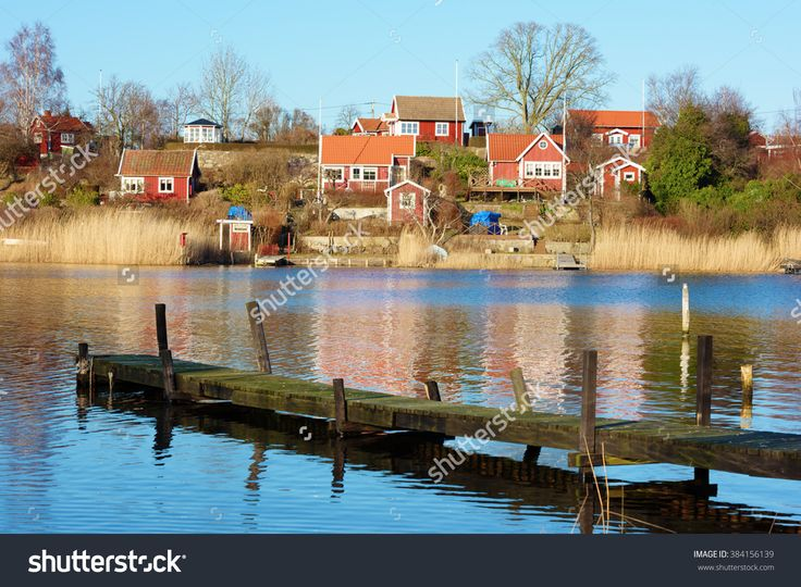 Brandaholm, Karlskrona, Sweden - February 26, 2016: The famous garden cottages on the islet are worth a visit even in early spring. A wooden pier in the foreground.