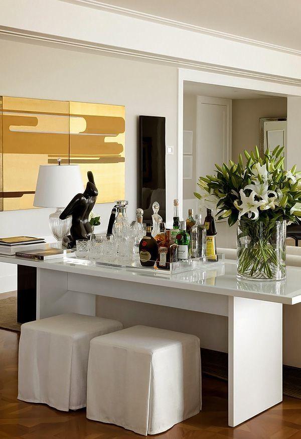 Já demos algumas dicas sobre como arrumar o espaço dobar em casa. Agora reunimos alguns ambientes com mesas e aparadores para disporas bebidas e criar um Bar em casa, neste aparador branco em laca.