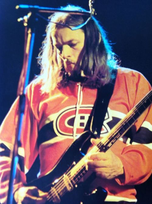 "David Gilmour | Pink Floyd wearing a jersey from the Montreal Canadiens hockey team. They were playing in Montreal, and there was a player named Doug Gilmour (same name as David's dad) so maybe it was his jersey... maybe it says ""Gilmour"" across the back."