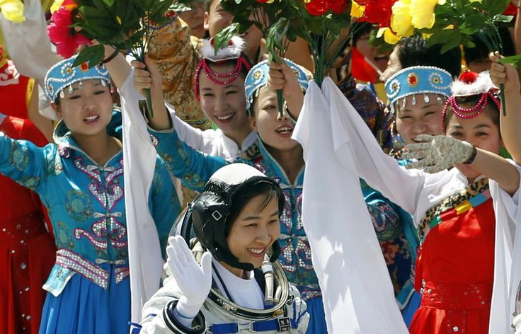 China's first female astronaut Liu Yang, bottom, waves June 16' 2012 during a sending off ceremony as she departs for the Shenzhou 9 spacecraft rocket launch pad at the Jiuquan Satellite Launch Center in Jiuquan, China.