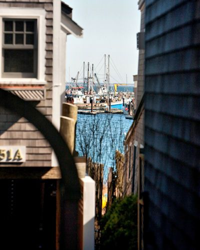 """P-Town Bay by FC Etier. """"Stop the car, Carole,"""" I said firmly. """"Back up just a bit … yeah, stop."""" I had been watching out the side window as we drove down Bradford Street in Provincetown, keeping my attention focused on the bay in the distance. As we passed this alley, I saw the shot I wanted."""