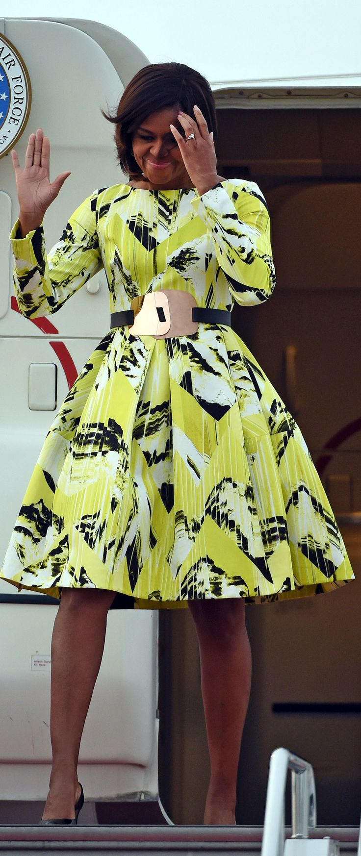 Michelle Obama arrives in Tokyo wearing an electric chartreuse Fall 2014 Kenzo dress, cinched at the waist with a Roksanda Ilincic belt 3.18.2015