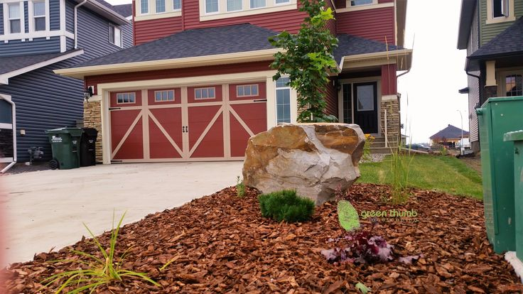 A well placed accent boulder makes a unique feature in an average sized front yard. The colours in this boulder tie into the house nicely.