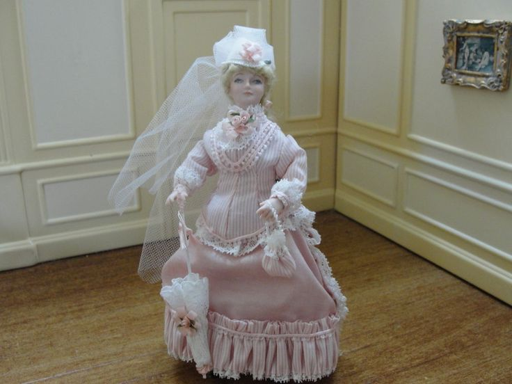 unknown artist - porcelain figure is wearing pink gown with a pink and white striped top. The bodice is trimmed with white lace and small pink rosettes and ribbons. She wears a white hat with pink ribbons and a long white net train. She carries a white lace parasol in one hand and a pink and white striped purse in her other hand. She wears white pantaloons and petticoat trimmed with lace and pink bows. She has poseable arms and legs, sold on ebay for $159