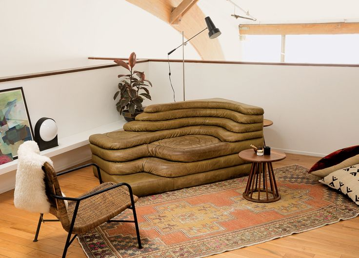 """In the bedroom sitting area, a chair by Dirk Van Sliedregt, a De Sede vintage Terrazza sofa by Ubald Klug (""""I plan to have a complete collection of four before I die"""") and a table by Arthur Umanoff."""
