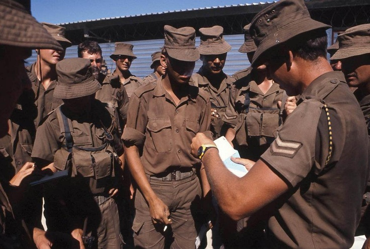 Mail Call. Regular mail, delivered to front-lines is key to maintaining an army's morale. Here SADF troops on the Angolan border receive this vital link with home and loved ones from their corporal. Photo - Outapi Museum.