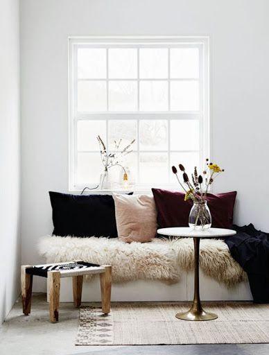 Platsbyggd soffa dekorerad med med fårskinn och kuddar