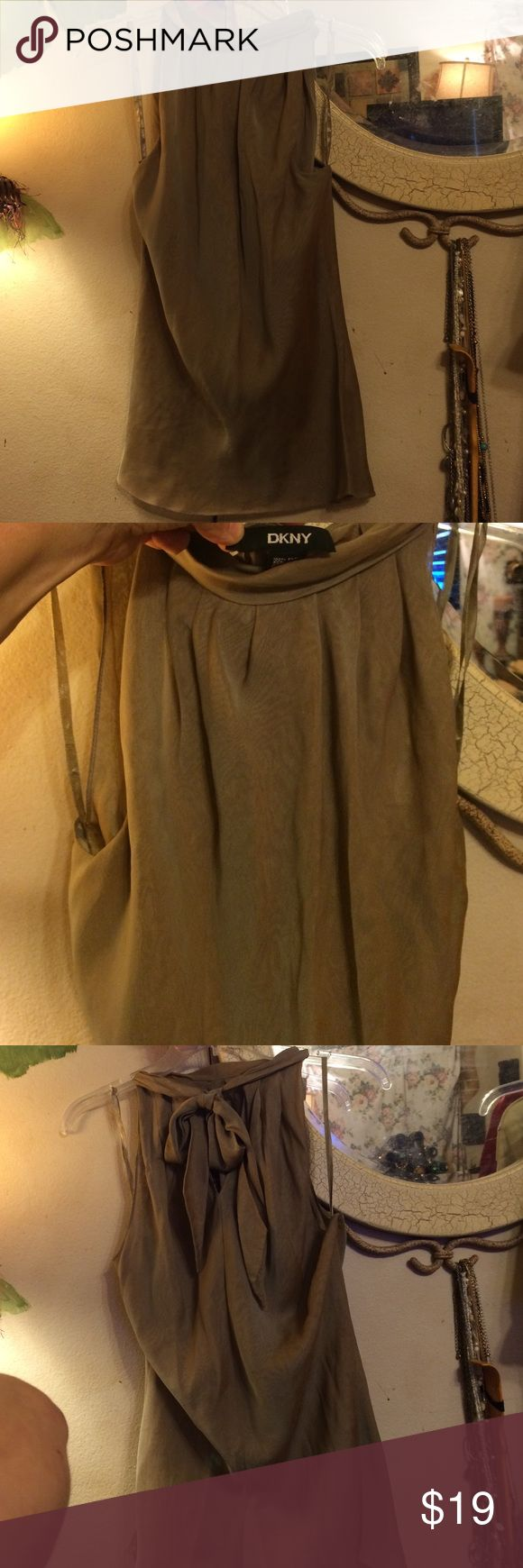 DKNY sleeveless beige blouse. DKNY beige sleeveless blouse with key hole design at back of neck where top is tied to complete the tops way it was designed to wear DKNY Tops Blouses