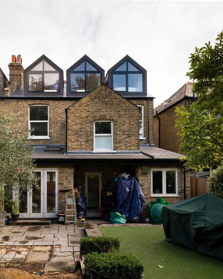 A Small Studio converted the existing roof space of this house and added a trio of dormer windows clad in zinc, with just 25 centimetres between them. Each of the large windows offers views of the back garden and to hills beyond.