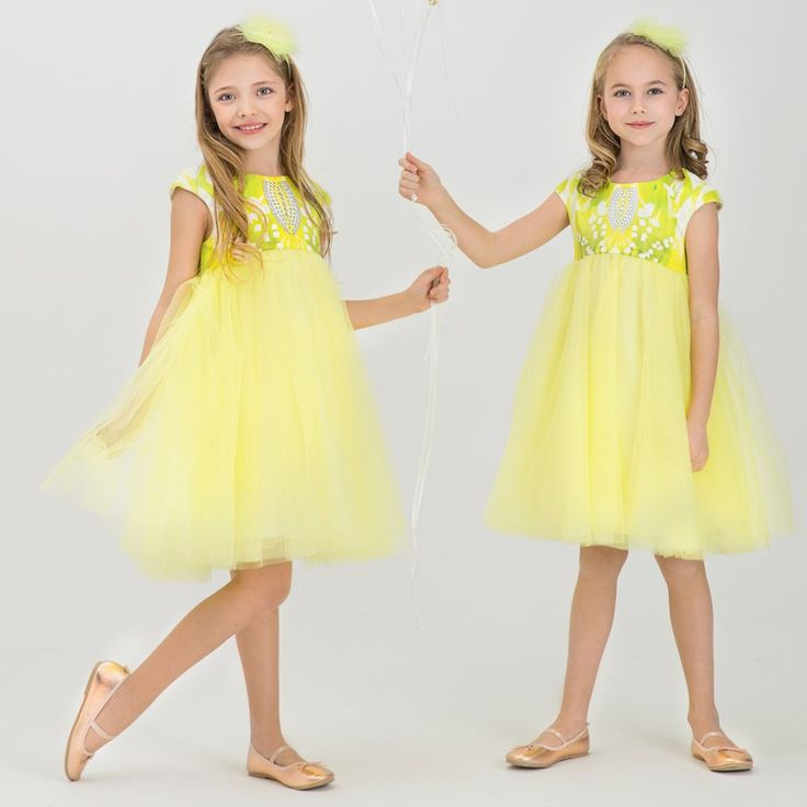 Girls striking yellow dress by Junona, with a satin bodice patterned with lily of the valley and butterflies, and embellished with a diamanté panel. Fully lined in soft, pale yellow, woven cotton, the skirt is made up of many layers of tulle for a full look, and there is a concealed zip fastener at the back. It comes with a matching yellow hairband, with a tulle and diamante flower.