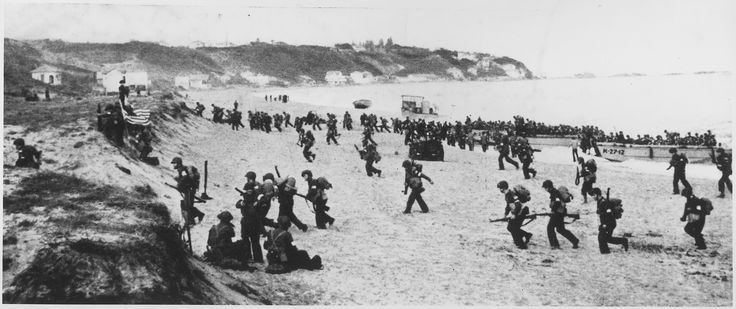 """Near Algiers, """"Torch"""" troops hit the beaches behind a large American flag """"Left"""" hoping for the French Army not fire on it."""