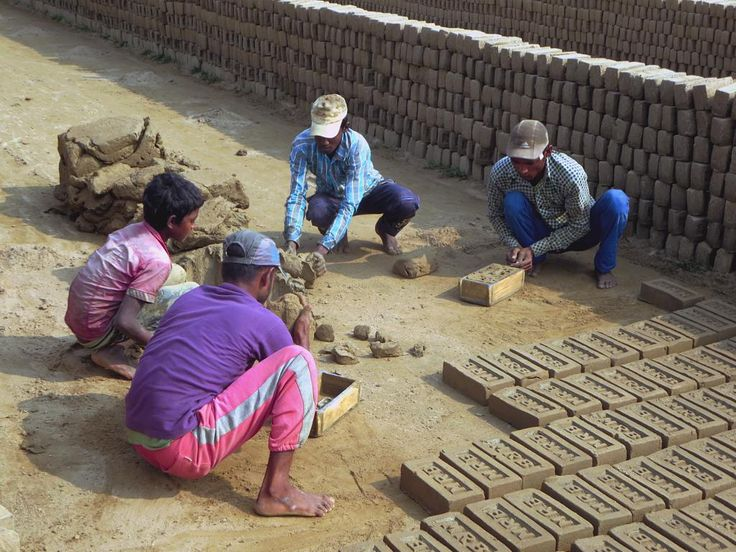 Bangladeshi workers form bricks from clay by hand and lay them out in the sun. Later the dried bricks are fired in ovens.