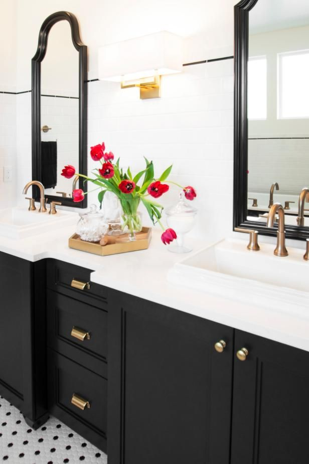 HGTV loves the classic, clean style of this updated bath with a dark wood vanity, white counters, contemporary sconces and a splash of color from red tulips.