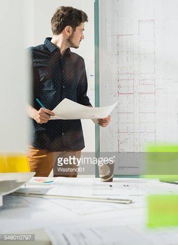 Stock Photo : Young architect in office looking at construction plan