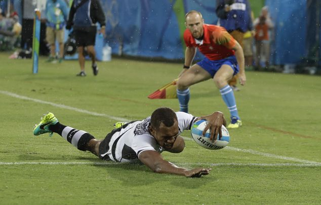 Fiji's Osea Kolinisau, scores a try during the men's rugby sevens match against…