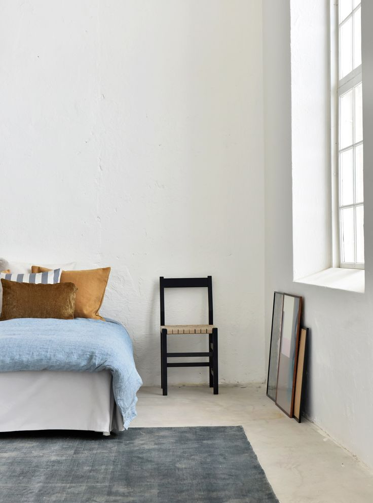 Texture is added to this minimal, industrial style loft with a plush rug and layered cushions | blue and brown is our favourite colour combination at the moment | white Bemz bedskirt | brown and acorn cushions | large industrial windows