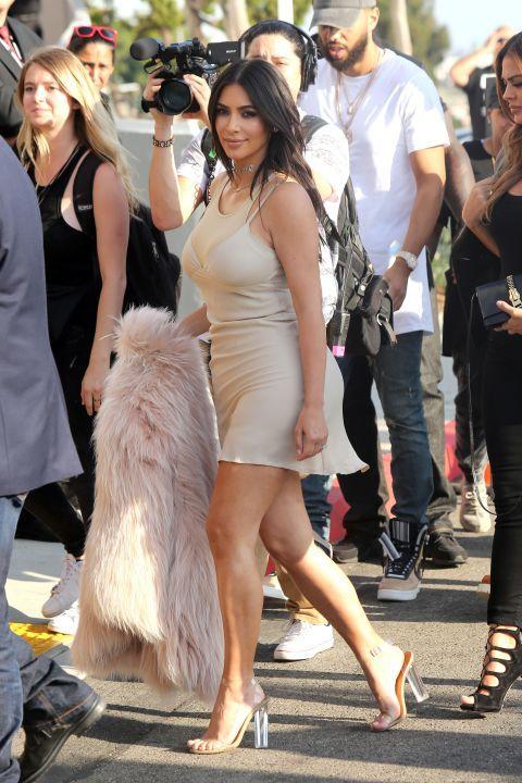 Kim Kardaishian attending Kanye's 'Famous' music video screening in LA, wearing a nude slip dress, pink fur coat and Yeezy sandals.