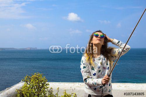 Beautiful young woman making selfie by selfiestick on seaside beach