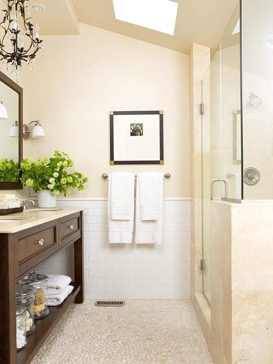make a small bathroom feel bigger - glass door with light stone surround, skylight, light neutral color scheme, open vanity area